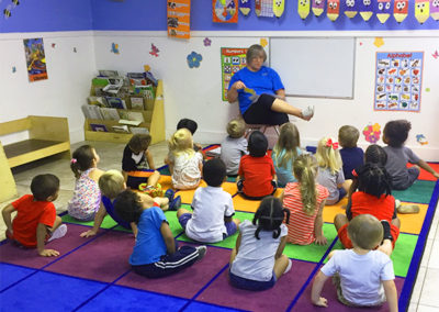 Pre-K children listening to a teacher tell a story at EduCare