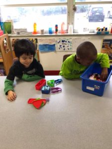 Two Toddlers are playing a game with numbers and shapes.